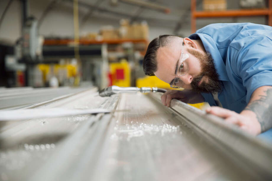 A worker examines sheet metal in a manufacturing plant. Photo: Hero Images, File / Getty / Hero Images