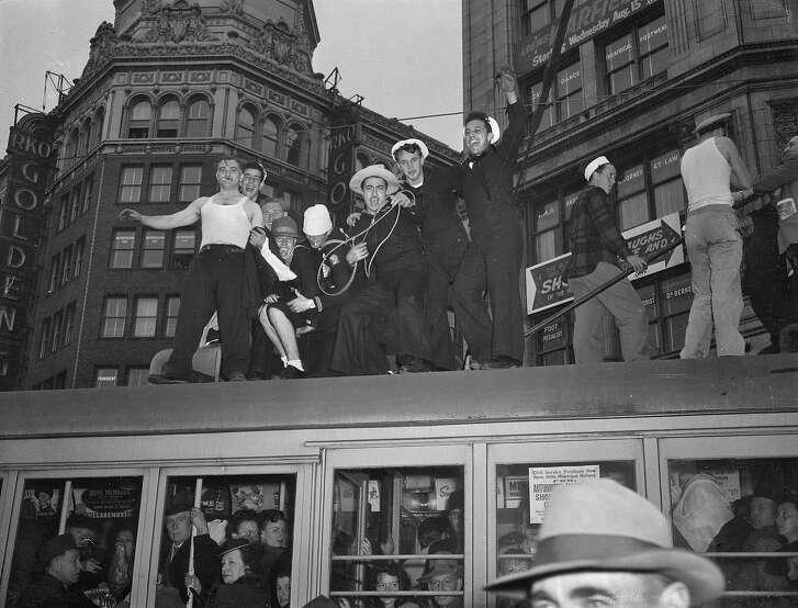V-J Day celebration in San Francisco ..August 14-15 1945 End of World War II, Japan surrenders  Men standing on top of a bus