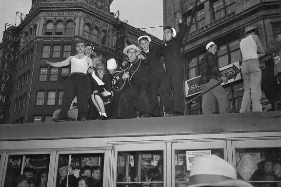 V-J Day celebration in San Francisco ..August 14-15 1945 End of World War II, Japan surrenders  Men standing on top of a bus