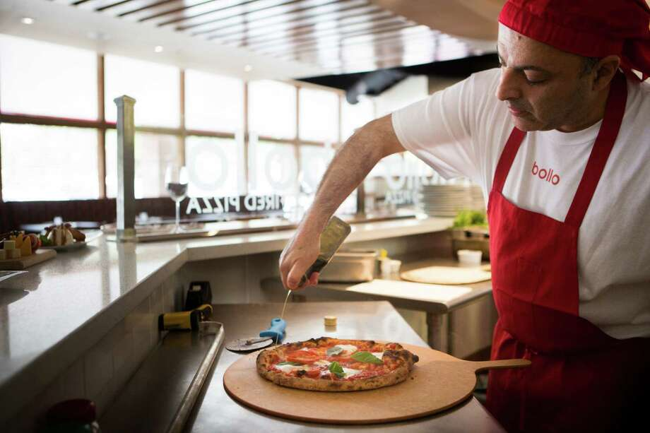 Ray Salti, the owner of Bollo Woodfired Pizza prepares the margarita pizza, made out of fresh basil, fresh tomatoes, buffalo mozzarella and EV olive oil. Wednesday, April 22, 2015, in Houston. Photo: Marie D. De Jesus, Houston Chronicle / © 2015 Houston Chronicle