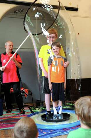 Brothers Jacob Ethier, 12, center, and Caleb Ethier, 9, right, of Niskayuna stand steady as bubble expert Jeff Boyer lifts a gigantic bubble around them during his Bubble Trouble show on Tuesday, July 15, 2014, at Troy Public Library in Troy, N.Y. (Cindy Schultz / Times Union) Photo: Cindy Schultz / 00027784A