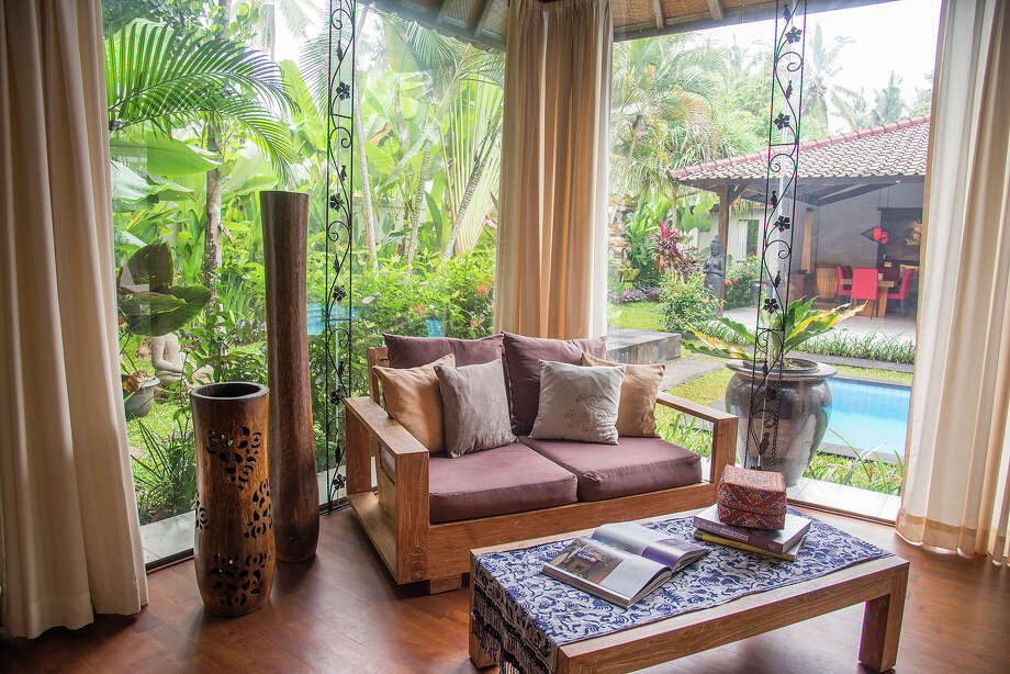 A sitting area adjoining the master bedroom of a 3,300-square-foot home on the market for $435,000 in Ubud, on Bali in Indonesia, April 18, 2015. The home is comprised of two open-air, Javanese-style buildings, the larger of which can be seen here beyond the swimming pool. Photo: Rony Zakaria/The New York Times / NYTNS