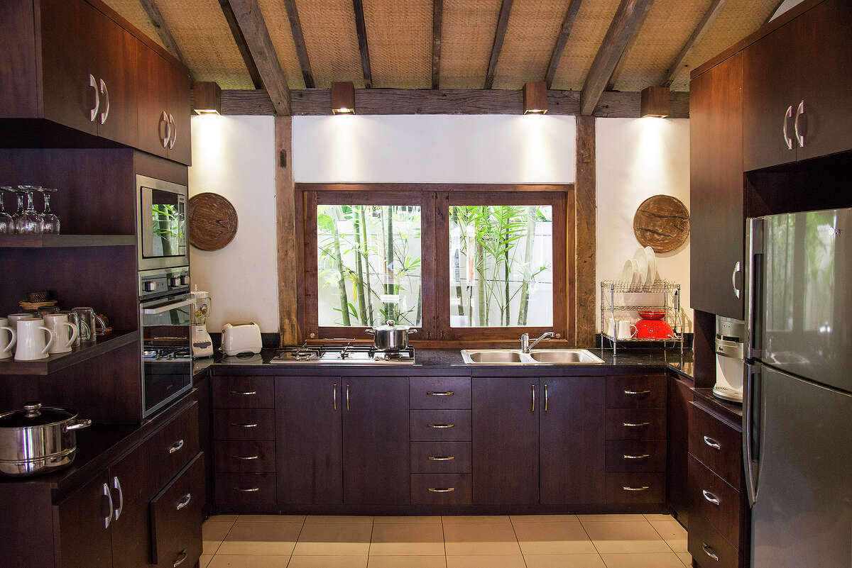 A kitchen with modern appliances in a traditional 3,300-square-foot home on the market for $435,000 in Ubud, on Bali in Indonesia, April 18, 2015. The home, two traditional Javanese-style joglo structures separated by a pool, is surrounded by gardens.