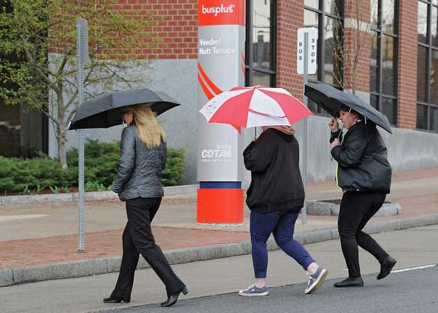 Three women cross State St. with umbrellas in the rain on Wednesday, April 22, 2015 in Schenectady, N.Y.  (Lori Van Buren / Times Union) Photo: Lori Van Buren