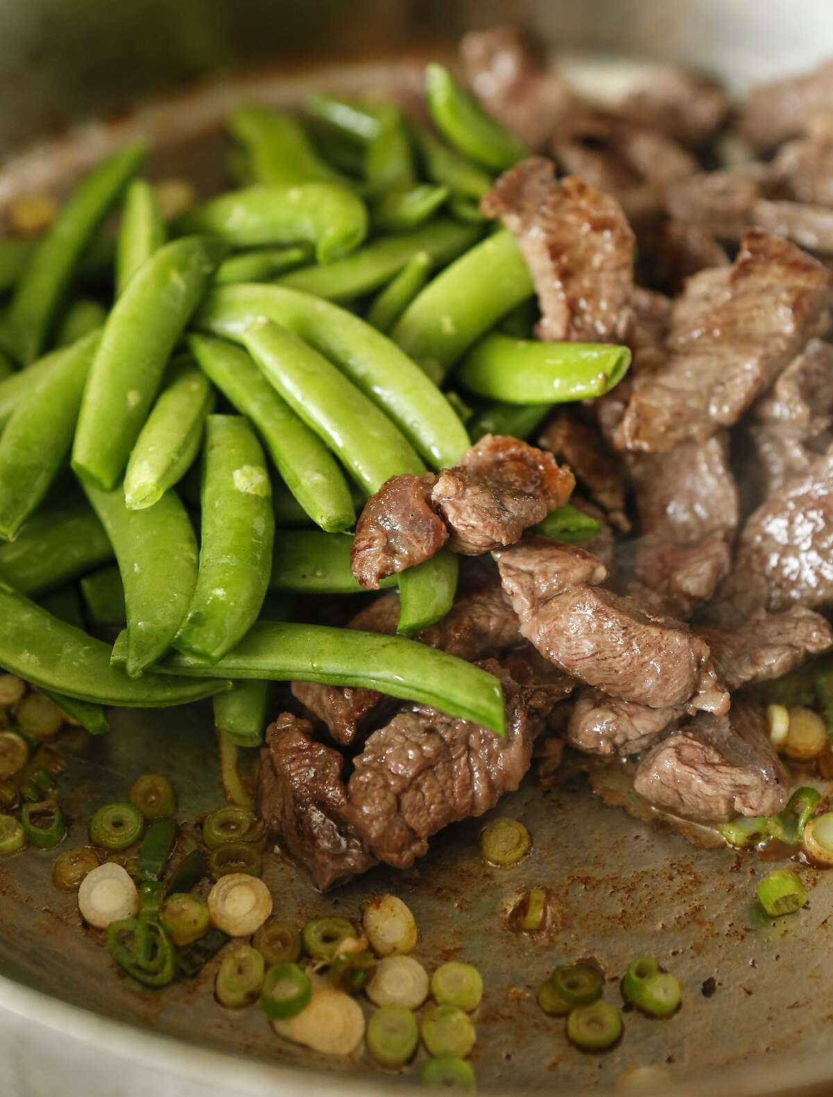 Steak and spring vegetable saute is seen in the pan on Wednesday, April 22, 2015 in San Francisco, Calif.