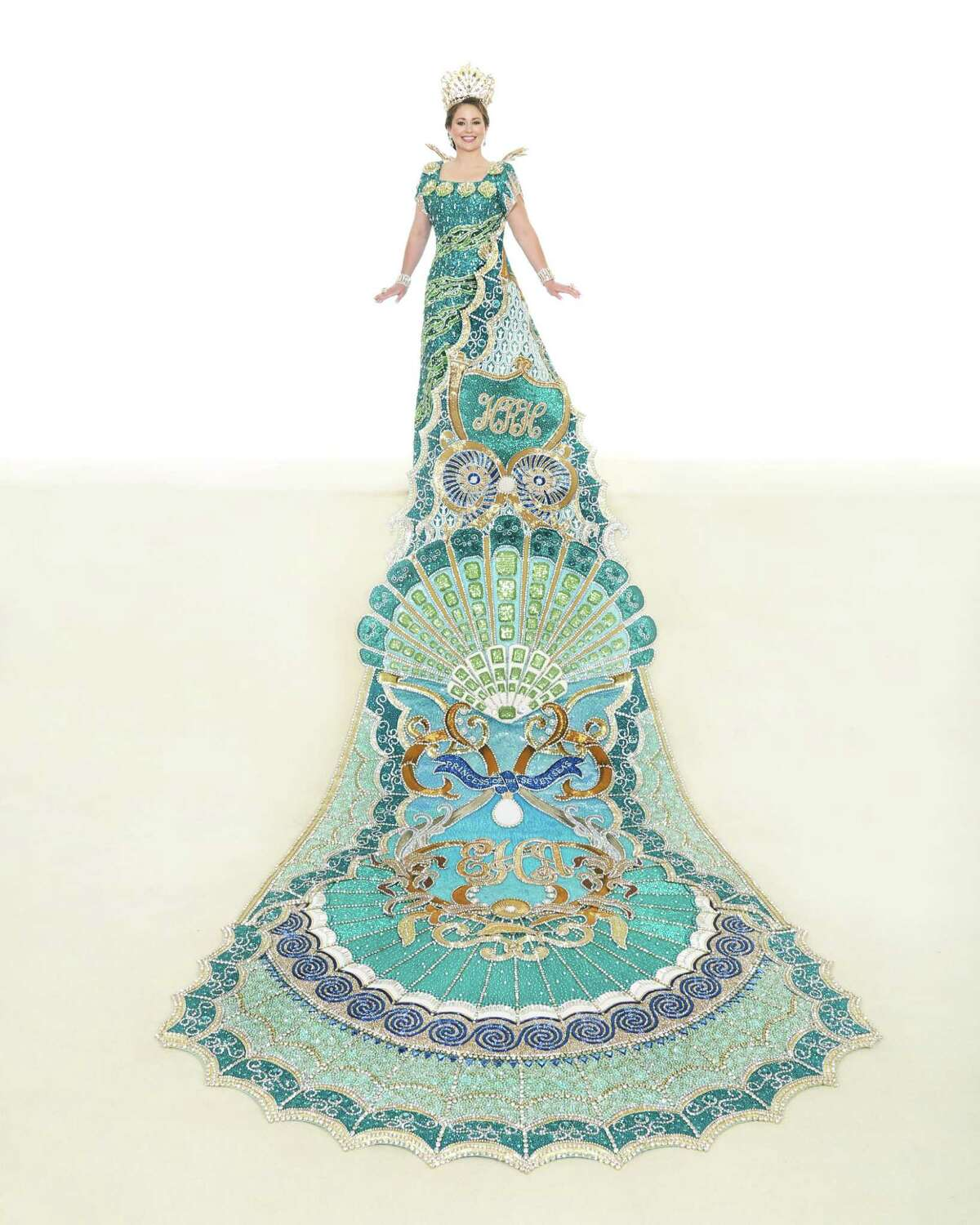 Princess Elizabeth Adaire Hughes, Princess of the Seven Seas: Representing the Seven Seas, the princess' gown is layered in shades of teal silk and embellished with several hues of sequins, blue zircon stones, crystals and drops of pearl. Scalloped shells of gold metallic lamé frame the neckline extending to the collar of metal featuring silver crystal navettes and rhinestone chain. The train of teal silk and metallic gold lamé is adorned with three stylized shells outlined with waves of crystal rhinestone chain. The princess is the daughter of Mr. and Mrs. Dan Allen Hughes Jr.
