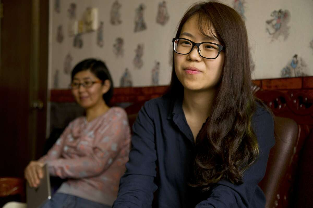 In this April 18, 2015 photo, the girlfriend of Chinese activist Li Tingting, who wished to be identified only by her English name of Teresa, right, speaks during an interview as she sits with Li's lawyer Wang Yu, left, in Beijing. Li, one of five recently released Chinese women's rights activists feels her dedication to activism has grown only stronger after spending 37 days in detention with interrogators who blew smoke onto her face and insulted her sexual orientation, her girlfriend and her lawyer said.