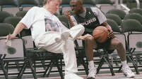 Spurs guard Avery Johnson gestures toward San Antonio businessman and former franchise owner Red McCombs in 1999 as they joke around and chat during the team's practice at the Alamodome.