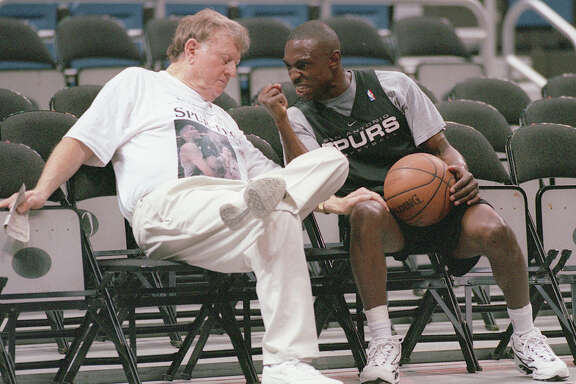 Spurs guard Avery Johnson, right, guestures toward San Antonio businessman and former Spurs owner Red McCombs on June 12, 1999 as they joke around and chat during the team's practice at the Alamodome.