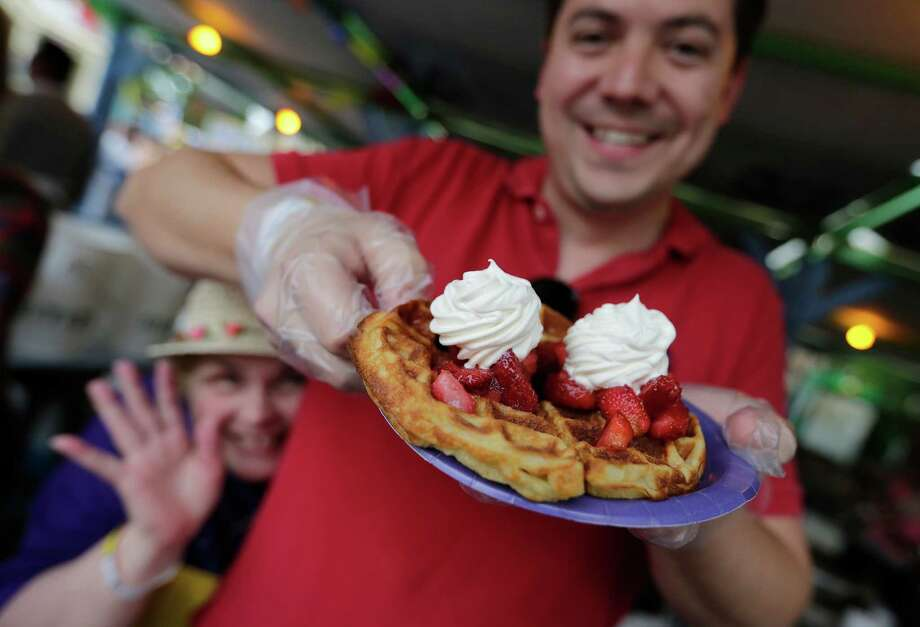 Carlos Jarquin and Carol Hughes have fun while serving up Belgian waffles at the 2015 A Night In Old San Antonio at La Villita on Tuesday, Apr. 21, 2015. The waffles are made right on the spot for the annual fiesta event which benefits the San Antonio Conservation Society. Photo: Kin Man Hui /San Antonio Express-News / ©2015 San Antonio Express-News