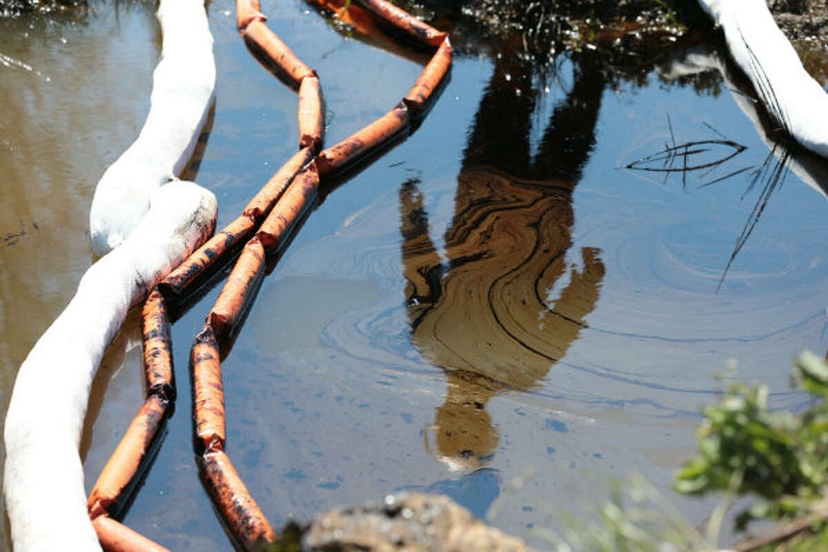A member of ExxonMobil's cleanup crew is reflected in water and oil in a drainage ditch along State Highway 365 in Mayflower, Ark., Monday, April 1, 2013. Cleanup in the area where thousands of barrels of crude oil leaked from a pipeline continues this week.