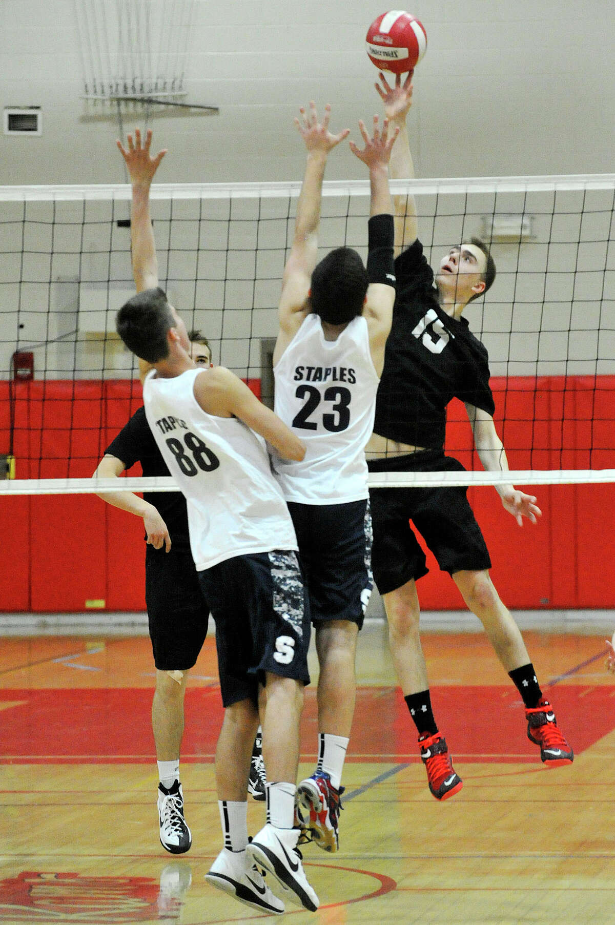 Staples' Keiran Simunovic (88) and Jason Bernstein (23) attempt to block the shot from New Canaan's Mikhail Dayton during their volleyball match at New Canaan High School in New Canaan, Conn., on Wednesday, April 22,2015.