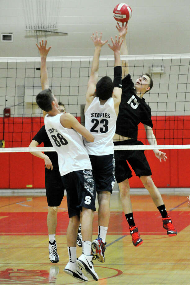 Staples' Keiran Simunovic (88) and Jason Bernstein (23) attempt to block the shot from New Canaan's Mikhail Dayton during their volleyball match at New Canaan High School in New Canaan, Conn., on Wednesday, April 22,2015. Photo: Jason Rearick / Stamford Advocate