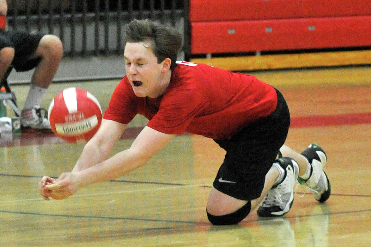New Canaan libero Matthew Donaldson makes a dig during the Rams' volleyball match against Staples at New Canaan High School in New Canaan, Conn., on Wednesday, April 22,2015.