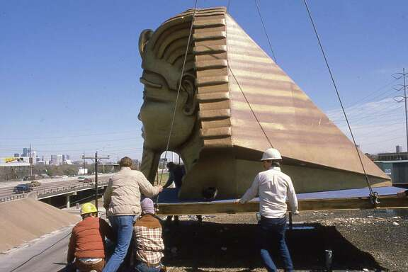 3/6/1984 - Workmen raise a fiberglass Egyptian head tot he top of the Magic Island club at 2215 Southwest Freeway. Owners of the private club say the restaurant will feature magic acts.