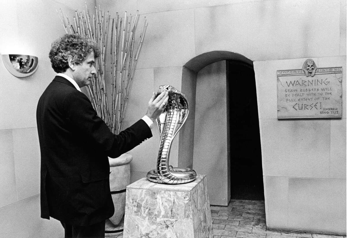 08/19/1986 - Richard Simon, vice president of Magic Island, inserts a membership card into the cobra's mouth to activate the tomb door leading to the inside of the magic club located at Southwest Freeway and Greenbriar.