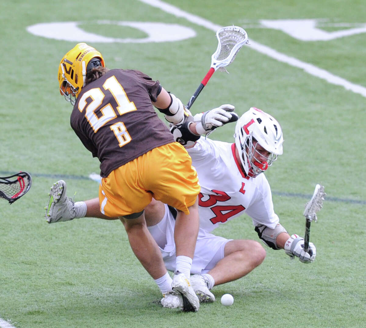 At left, John Fox (#21) of Brunswick takes down Lawrenceville's Charles Burditt (#34) with a check making Burditt lose the ball during the boys high school lacrosse match between Brunswick School and Lawrenceville School at Brunswick in Greenwich, Conn., Wednesday, April 22, 2015. Brunswick won the match, 18-8.