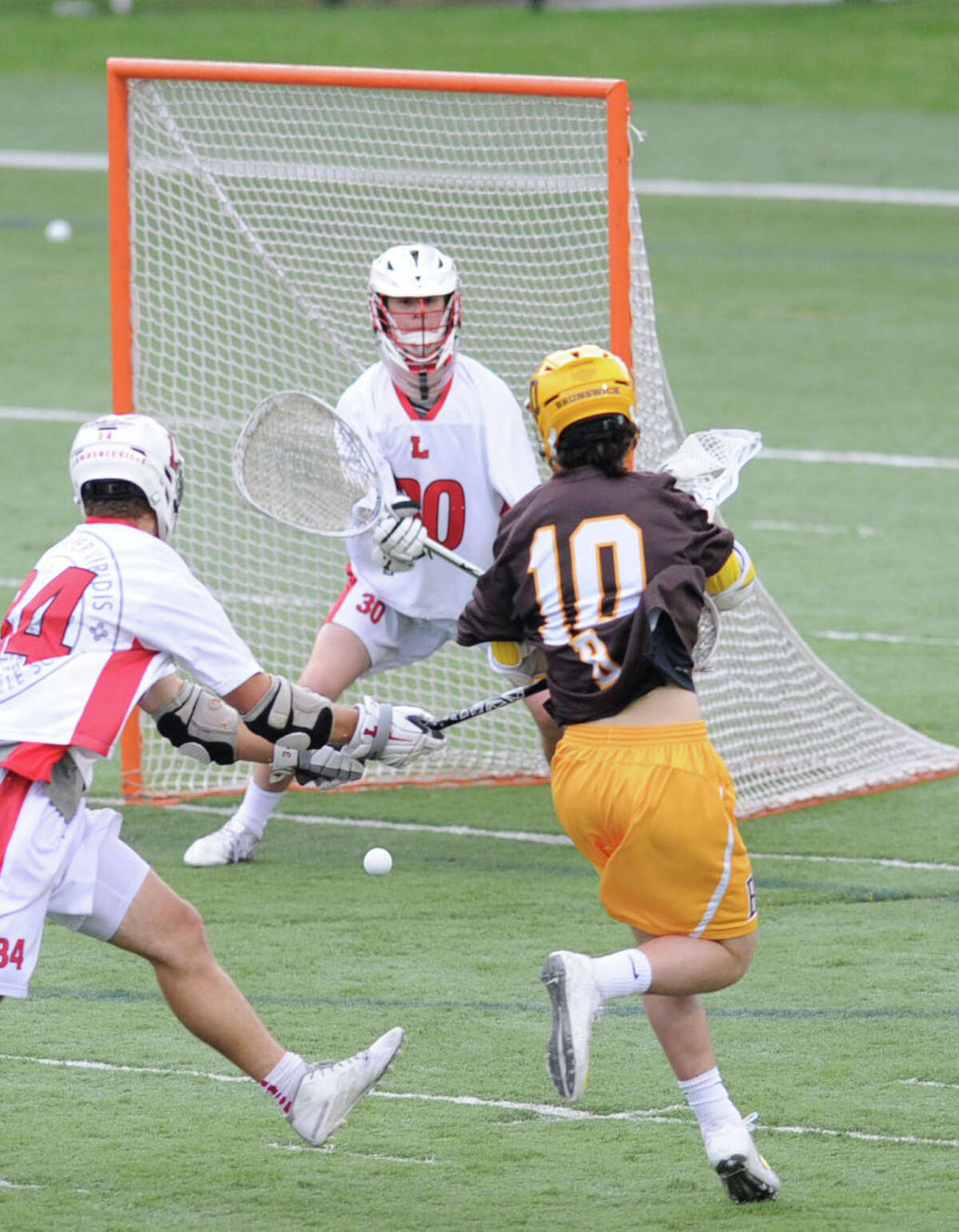 Lawrenceville goalie Miles Thompson, center, can not stop a goal by Brunswick's Sean Morris (#10) during the boys high school lacrosse match between Brunswick School and Lawrenceville School at Brunswick in Greenwich, Conn., Wednesday, April 22, 2015. Brunswick won the match, 18-8.