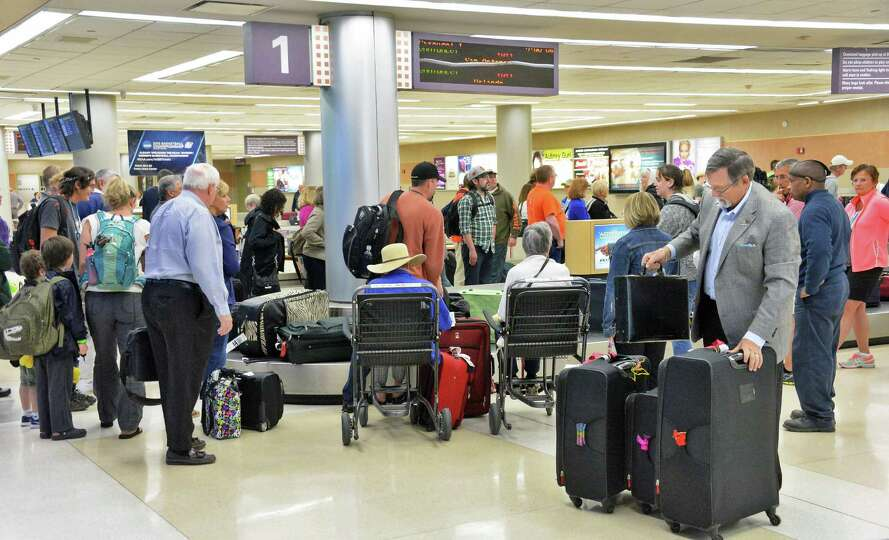 Travelers crowd the baggage claim at Albany International Airport Wednesday April 22, 2015 in Coloni