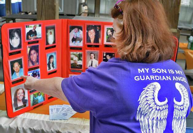 Helen Parola of Schenectady points to a photo of her son James Parola lost in an arson fire during the annual Ceremony of Remembrance of Homicide Victims in Central Park Wednesday April 22, 2015 in Schenectady, NY.  (John Carl D'Annibale / Times Union) Photo: John Carl D'Annibale / 00031493A
