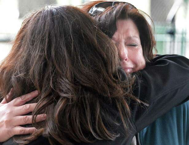 Margaret Messer, right, whose brother Brett Wentworth was murdered gets a hug from event coordinator Tina Mazzucco during the annual Ceremony of Remembrance of Homicide Victims in Central Park Wednesday April 22, 2015 in Schenectady, NY.  (John Carl D'Annibale / Times Union) Photo: John Carl D'Annibale / 00031493A
