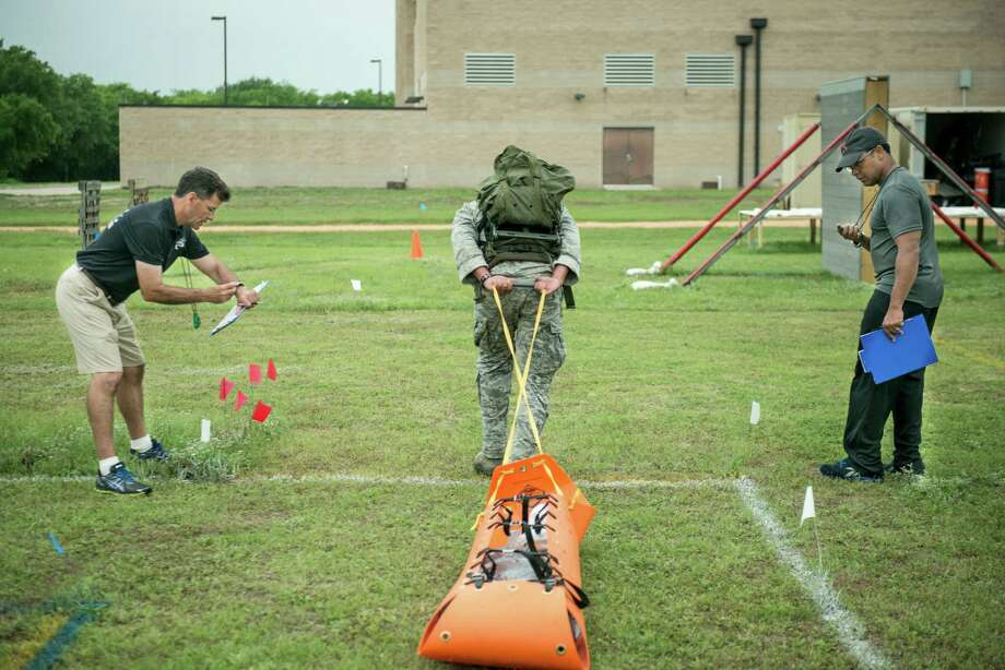 Neal Baumgartner, a former Air Force Major, left, and Sgt. Ron Davis, right, time an Air Force special operations volunteer carrying a weighted sled during a testing session for a new set of gender neutral physical standards for specific operational commands in the Air Force at Joint Base San Antonio-Lackland on Wednesday, April 22, 2015. Neal Baumgartner, a retired Air Force Major, along with the Air Force fitness testing and standards Unit is developing a new set of physical requirements for Airmen that will be based on the tasks that they must be able perform in their posts. The program will aim to include a large percentage of women after the 2013 announcement that the Air Force would open six previously closed career fields to female applicants. The Air Force currently has ninety-nine percent of their career fields open to both men and women. The remaining fields are in ground combat and special operations. Photo: Matthew Busch, Photojournalist / © Matthew Busch, 2012