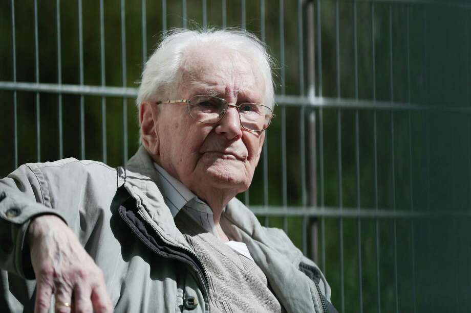 Former SS guard Oskar Groening sits in ths sun during the noon break of the trial against him in Lueneburg, northern Germany, Tuesday, April 21, 2015.  93-years-old Groening faces 300,000 counts of accessory to murder at the trial, which will test the argument that anyone who served as a guard at a Nazi death camp was complicit in what happened there. Groening said he bears a share of the moral guilt for atrocities at the camp, but told judges it is up to them to decide whether he deserves to be convicted as an accessory to murder.  (AP Photo/Markus Schreiber) Photo: Markus Schreiber, STF / Associated Press / AP