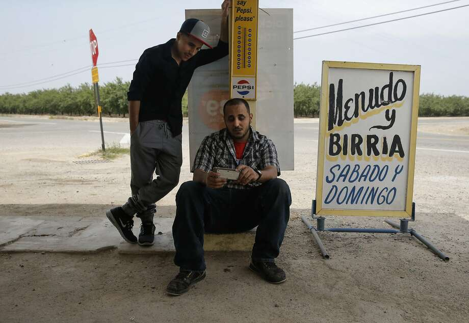 Jaffar Mohsen, (left) and his brother-in-law Fathi Hussein, (left)  get much of their information out of Yemen from social media sites on their smart phones as seen outside Bonita Market which is run by Jaffar in Madera, Calif., on Wed. April 22, 2015. Family members of Fathi Hussein and Jaffar Mohsen have been unable to leave Yemen as fighting within the country has escalated since they arrived in February for a family vacation. Photo: Michael Macor, The Chronicle