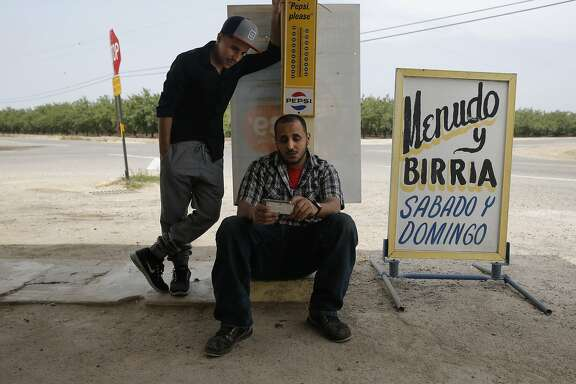 Jaffar Mohsen, (left) and his brother-in-law Fathi Hussein, (left)  get much of their information out of Yemen from social media sites on their smart phones as seen outside Bonita Market which is run by Jaffar in Madera, Calif., on Wed. April 22, 2015. Family members of Fathi Hussein and Jaffar Mohsen have been unable to leave Yemen as fighting within the country has escalated since they arrived in February for a family vacation.