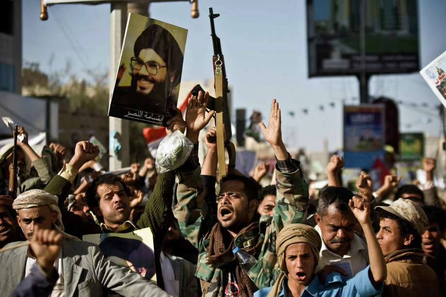 A Shiite rebel known as a Houthi, second left, holds a poster of Hezbollah leader Sheikh Hassan Nasrallah as he attends along with his comrades a protest to denounce the Saudi aggression in Sanaa, Yemen, Wednesday, April 22, 2015. Yemen's Shiite rebels, who have taken over large parts of the country and have faced a Saudi-led air assault, said Wednesday they welcome United Nations-led talks to find a political solution to the conflict.  (AP Photo/Hani Mohammed) Photo: Hani Mohammed, STR / Associated Press / AP