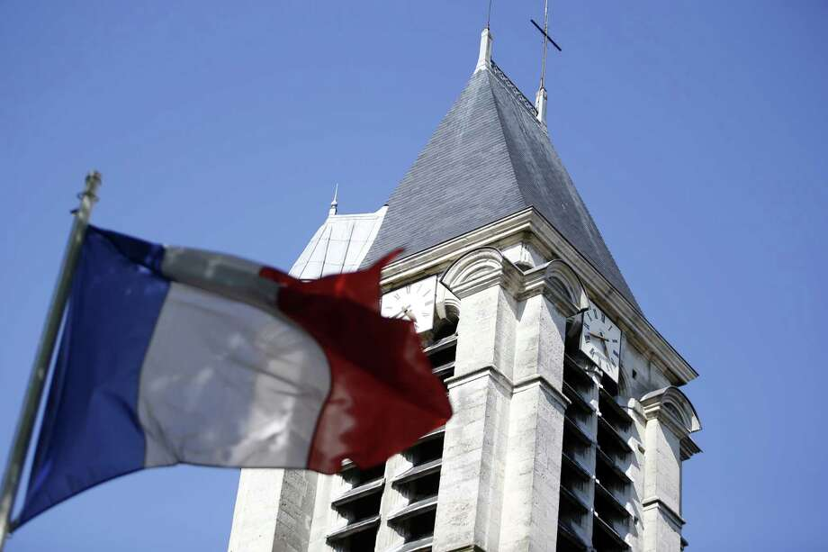 The steeple of the Saint-Cyr and Sainte-Julitte church is seen behind a French national flag on April 22, 2015, in Villejuif, outside Paris. This church was probably a target of Sid Ahmed Ghlam, a student suspected of planning to attack a church in France, who was arrested on April 19, 2015. French police found Arabic documents mentioning the Islamic State group and Al-Qaeda at his home, the Paris prosecutor said on April 22. The 24-year-old Franco-Algerian's plans were exposed purely by chance after he called an ambulance over a bullet injury to his leg. Police traced a trail of Sid Ahmed Ghlam's blood to his car, where they discovered an arsenal of weapons, Interior Minister Bernard Cazeneuve told reporters. AFP PHOTO / KENZO TRIBOUILLARDKENZO TRIBOUILLARD/AFP/Getty Images Photo: KENZO TRIBOUILLARD, Staff / AFP / Getty Images / AFP PHOTO