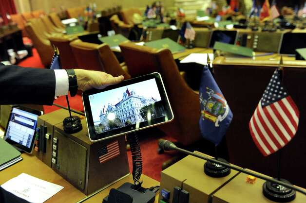 Assemblyman Jim Tedisco shows how the new tablet is attached to his desk in the Assembly Chamber on Wednesday, April 22, 2015, at the Capitol in Albany, N.Y.  The Assembly will use the tablets for the first time on Earth Day in place of paper bills. (Cindy Schultz / Times Union) Photo: Cindy Schultz / 00031574A