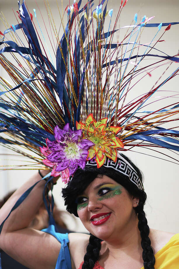 Leora Uribe adjust her headdress before the start of the second of three days of Cornyation at the Charline McCombs Empire Theatre, Wednesday, April 22, 2015. The event can be traced back to 1951 when it was staged at the San Antonio Little Theater at the Arneson River Theater as part of Night in Old San Antonio. Uribe represented a Mestizo at the Alamo for the Someone Coming in the Air Tonight skit. Photo: JERRY LARA, San Antonio Express-News / © 2015 San Antonio Express-News