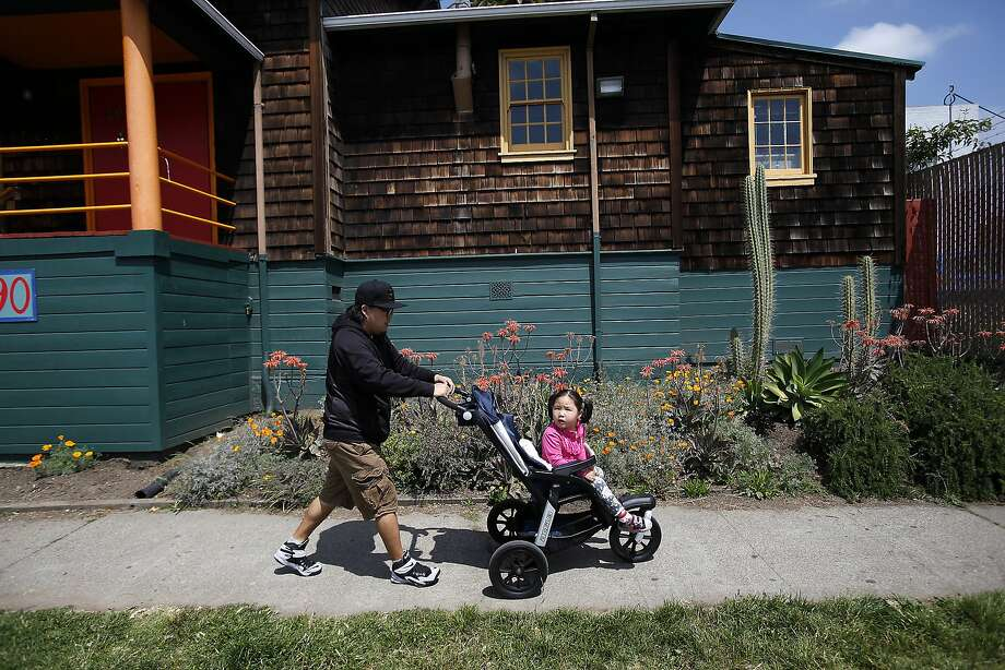 Gan-Erdene Ganbat and his daughter Nomin, 4, walk through their neighborhood in Oakland, Calif., on Wednesday, April 22, 2015. They moved from Mongolia to Oakland last November so Nomin, who has a rare genetic disease, can participate in a clinical trial that her parents hope will save her life.  She needs a full-time caregiver so her father spends all of his time looking after her.  Her mother was denied a visa. Photo: Sarah Rice, Special To The Chronicle