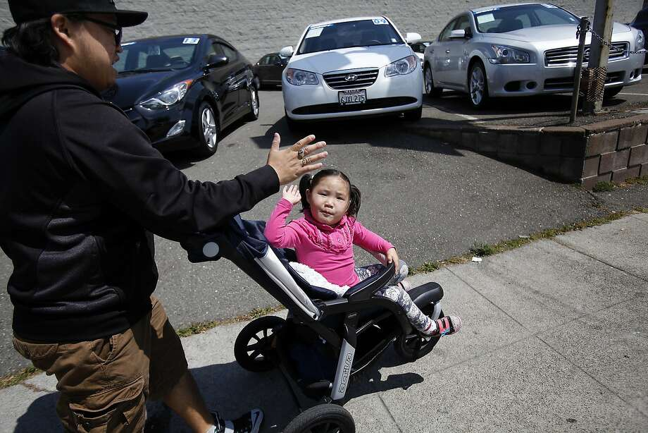 Gan-Erdene Ganbat gives his daughter Nomin, 4, a high-five as they walk through their neighborhood in Oakland, Calif., on Wednesday, April 22, 2015. They moved from Mongolia to Oakland last November so Nomin, who has a rare genetic disease, can participate in a clinical trial that her parents hope will save her life.  She needs a full-time caregiver so her father spends all of his time looking after her.  Her mother was denied a visa. Photo: Sarah Rice, Special To The Chronicle