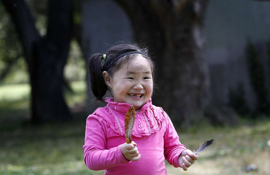 Nomin Gan-Erdene, 4, plays in the park in Oakland, Calif., on Wednesday, April 22, 2015. She moved from Mongolia  to Oakland with her father last November so she can participate in a clinical trial that her parents hope will save her life.  She needs a full-time caregiver so her father spends all of his time looking after her.  Her mother was denied a visa. Photo: Sarah Rice, Special To The Chronicle