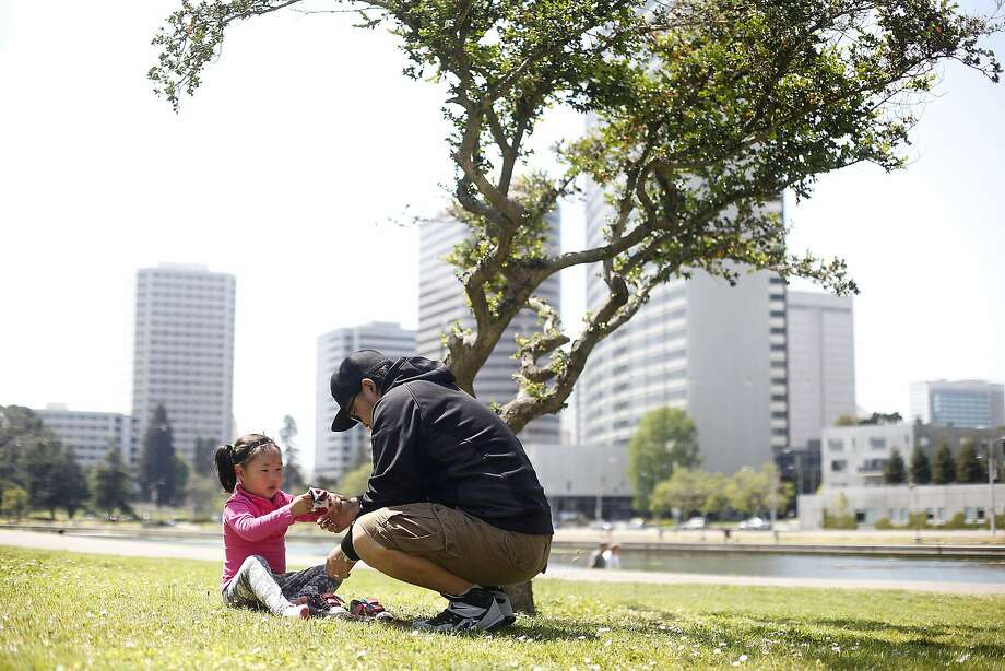 Gan-Erdene Ganbat and his daughter Nomin, 4, play near Lake Merritt in Oakland, Calif., on Wednesday, April 22, 2015. They moved from Mongolia to Oakland last November so Nomin, who has a rare genetic disease, can participate in a clinical trial that her parents hope will save her life.  She needs a full-time caregiver so her father spends all of his time looking after her.  Her mother was denied a visa. Photo: Sarah Rice, Special To The Chronicle