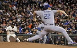 Joaquin Arias (13) leans off first as Clayton Kershaw (22) pitches in the third inning as the San Francisco Giants played the Los Angeles Dodgers at AT&T Park in San Francisco, Calif., on Wednesday, April 22, 2015.