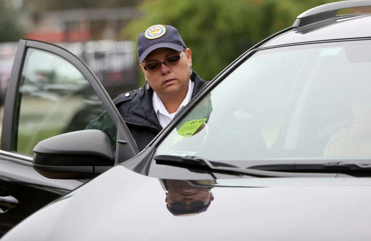 Irene Aguilar, regulatory investigator of the Administration and Regulatory Affairs Division, places on the windshield a Transportation Network Company vehicle for hire license permit, a new requirement, through the City of Houston's Administration and Regulatory Affairs Division at the Kashmere Multi-Service Center Thursday, Nov. 6, 2014, in Houston, Texas. Drivers also had their vehicles inspected for safety.