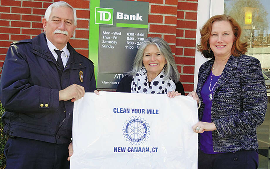 From left to right shown here are Fire Marshal/Rotary Club member Fred Baker,  Jenny Esposito of TD Bank, and Kathleen Holland, director of Inland Wetlands and Watercourses holding up a plastic bag available to volunteers for ìClean Your Mile,î ña town-wide spring clean up effort coinciding with the week of Earth Day. Photo: Contributed Photo / New Canaan News