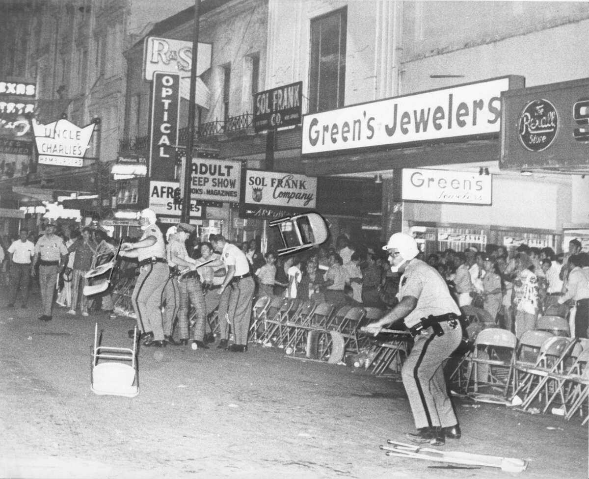 """From the News, April 26, 1971: """"Chairs fly through air during Fiesta Flambeau fight..."""" while policemen are shown on E. Houston Street trying to restore order. Note that editors had highlighted the thrown chair in the middle of the photo by drawing an outline with black pen."""