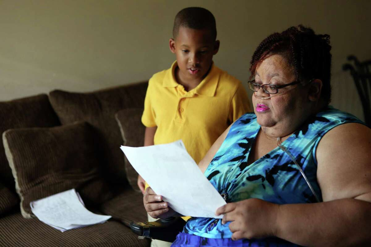 Jordan Melancon, 10, shows his school work to his grandmother Chrystal Jenkins-Washington, 56, on Tuesday, April 14, 2015, in Houston. Jenkins-Washington, unhappy with her neighborhood school and is considering transferring Jordan to a new school. She said his grades have slipped and he gets picked on at Woodson.