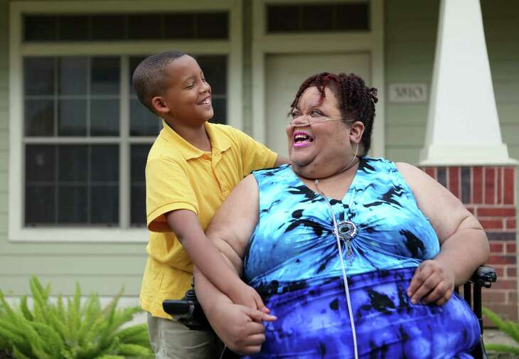 Jordan Melancon, 10, and grandmother Chrystal Jenkins-Washington, 56, share a moment outside her home on Tuesday, April 14, 2015, in Houston. Jenkins-Washington, unhappy with her neighborhood school, Woodson, said she is considering trying to transfer Jordan to a new school. She said his grades have slipped and he gets picked on at Woodson.