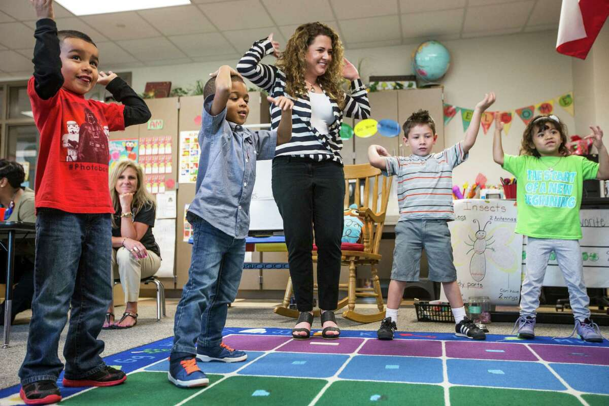 Vanessa de Simone Canseco, center, dances with students, from left, Julian Moreno, Braylon Nicholson, Ezequiel Portillo and Hailey Barrientos during a lesson at Marshall Elementary School on Friday, April 17, 2015, in Spring.
