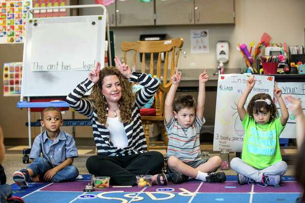 Pre-K teacher Vanessa de Simone Canseco sits with her students, from left, Braylon Nicholson, Ezequiel Portillo and Hailey Barrientos, during a lesson at Marshall Elementary School on Friday, April 17, 2015, in Spring.