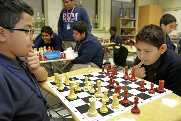 Sixth graders Joseph Mazariego, 12, left, and Roland Reyes, 12, right, play chess during their lunchtime at Baylor College of Medicine Academy at Ryan, 2610 Elgin, Thursday, April 16, 2015, in Houston.