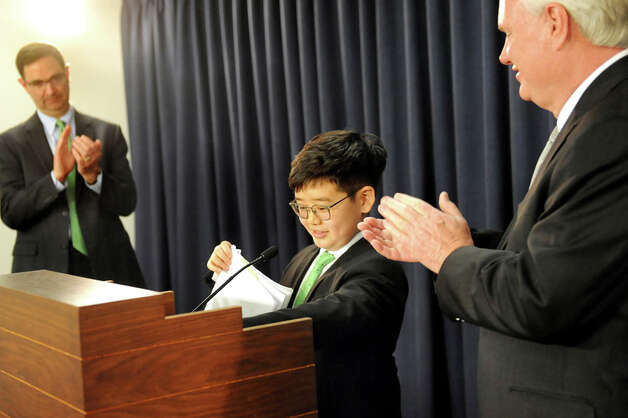 Eliot Seol , 10, of Queens, center, wraps up his comments about the Battery Recycling Bill to the applause of Peter M. Iwanowicz of Environmental Advocates, left, and Sen. Tony Avella during a news conference on Wednesday, April 22, 2015, at the Capitol in Albany, N.Y. (Cindy Schultz / Times Union) Photo: Cindy Schultz, Albany Times Union / 00031563A