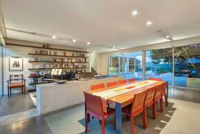 The reading nook includes built-in shelving is separated from the dining area by a concrete island.