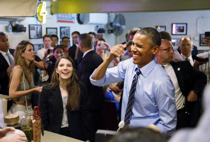 President Barack Obama has a moment with people when he visits Franklin Barbecue in Austin, Texas, Thursday, July 10, 2014. Left is Kinsey Button who is a student at the University of Texas at Austin, and wrote the President a letter in January explaining her family's struggle to lead a middle class life when both of her parents lost their jobs in the wake of the Great Recession. (AP Photo/The Dallas Morning News, Kye R. Lee, Pool)