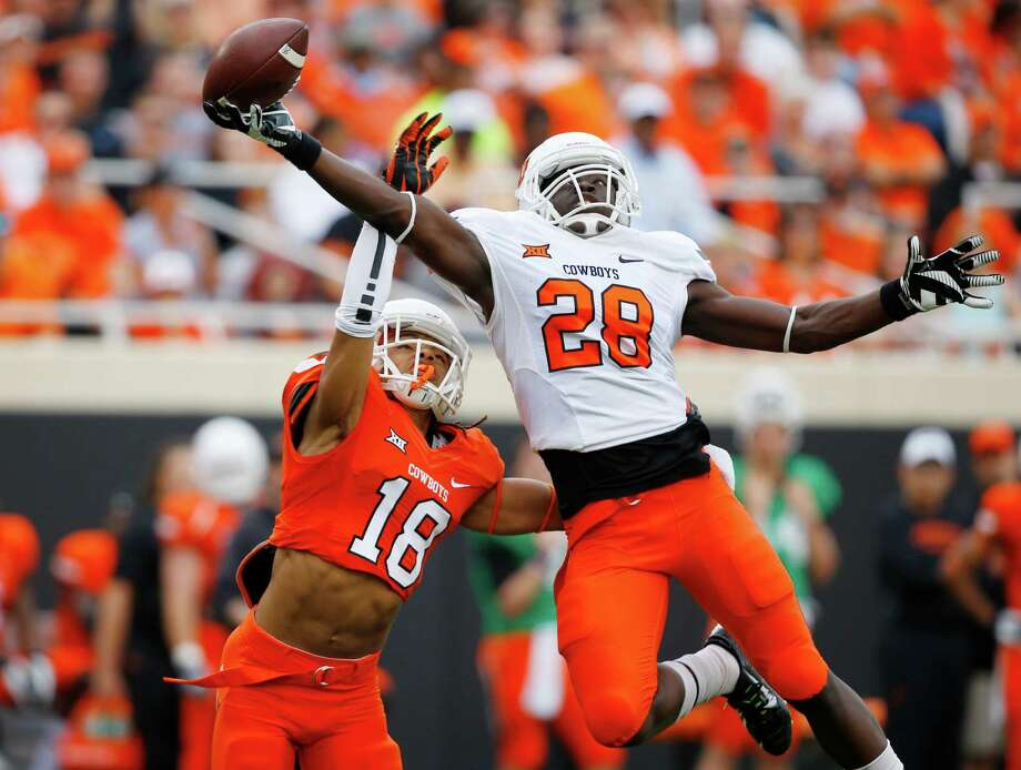 Oklahoma State wide receiver James Washington (28) catches a pass in front of defender Ramon Richards (18) in the first half of the Oklahoma State NCAA college spring football game Stillwater, Okla, Saturday, April 18, 2015. Photo: Sue Ogrocki /Associated Press / AP